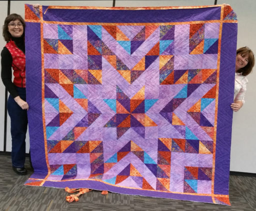 Quilt in lavenders with orange, red, and purple half square triangles forming a central varigated star, surrounding lavender star, and alternating colored and lavender blocks surrounding the central stars.  The quilt is bordered in orange and deep purples.
