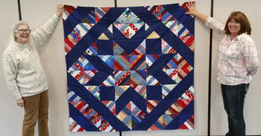 Quilt of reds, whites, and blue strips with solid navy sections forming a pattern of a central star and large navy diamond border.