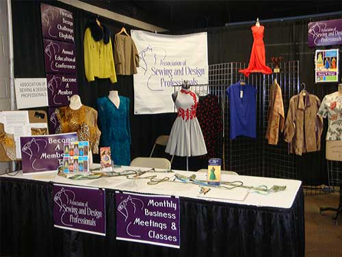 The ASDP booth for 2018 was large, giving plenty of space to exhibit ten garments made by the members of the group.  The table in front has samples of fancy trims and brochures for upcoming group events.