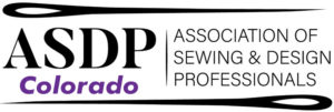 A mostly black and white logo with a pair of sewing needles above and below.  The letters A S D P are on the left and the words Association of Sewing and Design Professionals is on the right.  The word Colorado in purple is written under the letters A S D P.