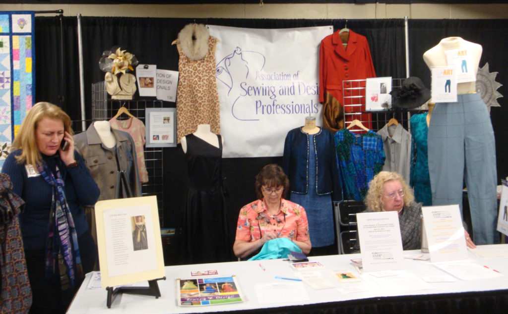 Image of three members working at 2019 Sewing Expo,  In the background are garments made by members of ASDP.